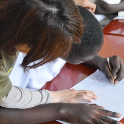 A female intern from Projects Abroad is pictured helping a young boy learn how to write whilst on her speech therapy internship in Tanzania.